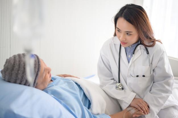 Uma mulher paciente com câncer usando lenço na cabeça após consulta de quimioterapia e médico visitante no hospital.