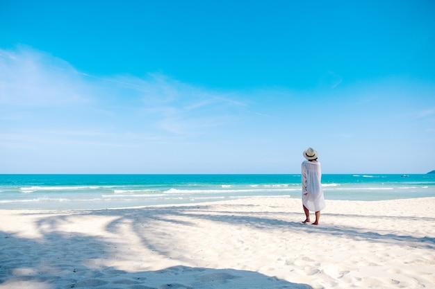 Uma mulher passeando na praia com o mar e o céu azul de fundo