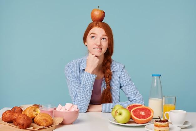 Uma mulher pensando em uma alimentação adequada está sentada à mesa