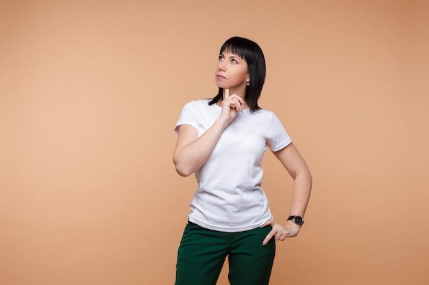 Uma mulher pensativa em t-shirt branca, olhando para cima.