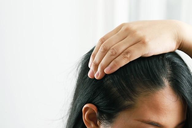 Uma mulher penteia o cabelo para explorar a caspa e o couro cabeludo.