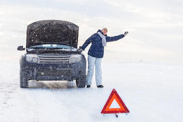 Uma mulher perto de um carro quebrado. ela está pedindo ajuda. perto do inverno e do campo de neve. existe um sinal de emergência.
