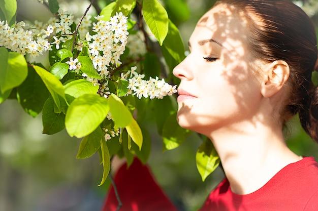 Uma mulher perto de uma cereja de pássaro de florescência