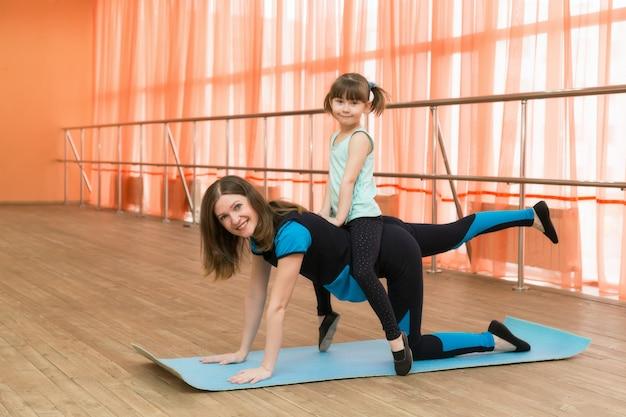 Uma mulher pratica esportes com uma criança nas costas.