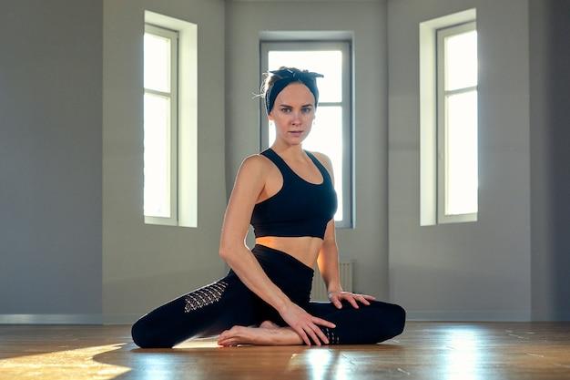 Uma mulher pratica ioga em uma sala de fitness ao amanhecer