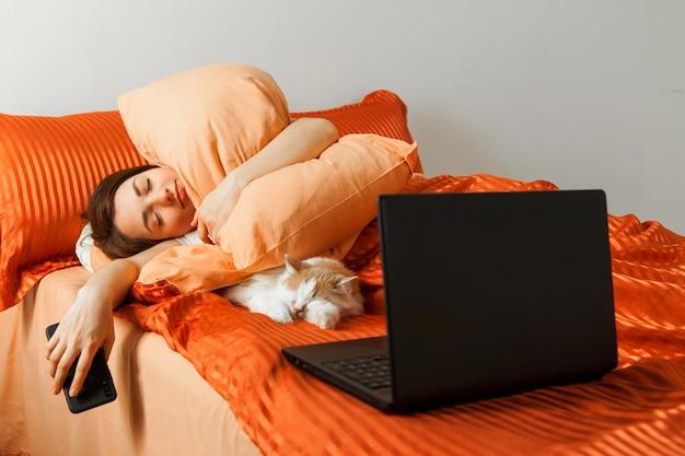 Uma mulher preguiçosa dorme em uma cama com um laptop sobre os joelhos e um gato dormindo nas proximidades.