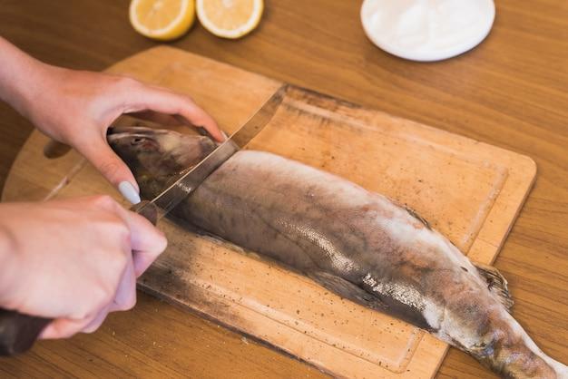 Uma mulher prepara peixe, cortando peixe em uma placa de madeira, o cozinheiro tempere a truta