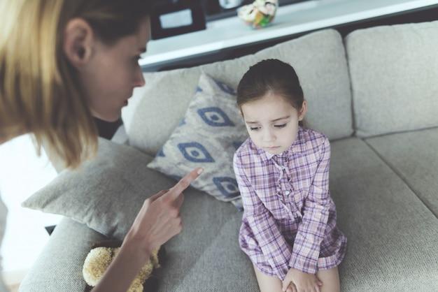 Uma mulher pune uma menina e faz uma careta no dedo.