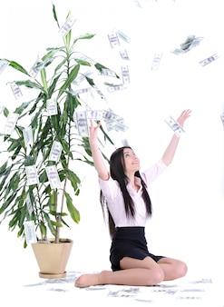 Uma mulher que alcança acima da colheita do dinheiro fora de uma árvore.