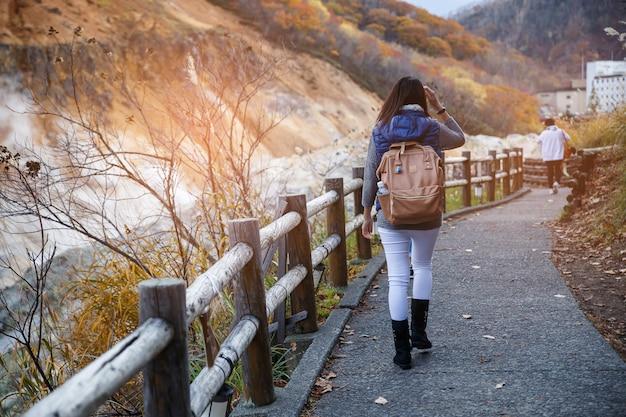Uma mulher que anda na rua e na árvore de bordo amarela vermelha na estação do outono, tomada de japão.