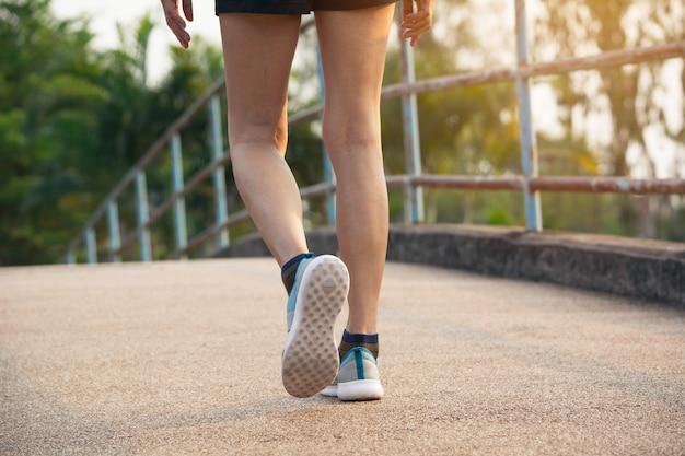 Uma mulher que corre na manhã para movimentar-se, exercitando e conceito saudável do estilo de vida.