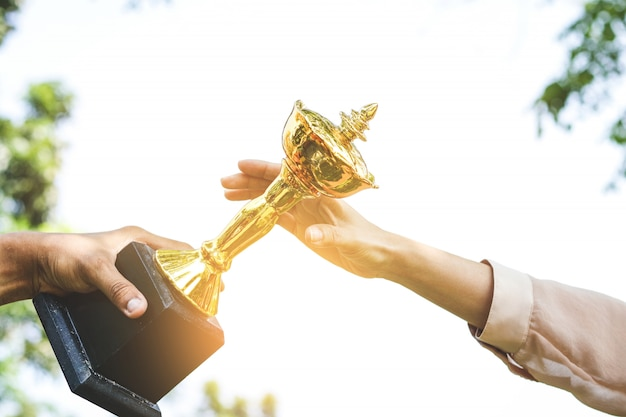 Uma mulher que detém um troféu de ouro de seus talentos faz dele um sucesso.
