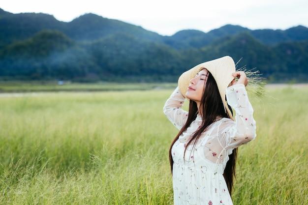 Uma mulher que está segurando uma grama nas mãos em um belo campo de grama com uma montanha.