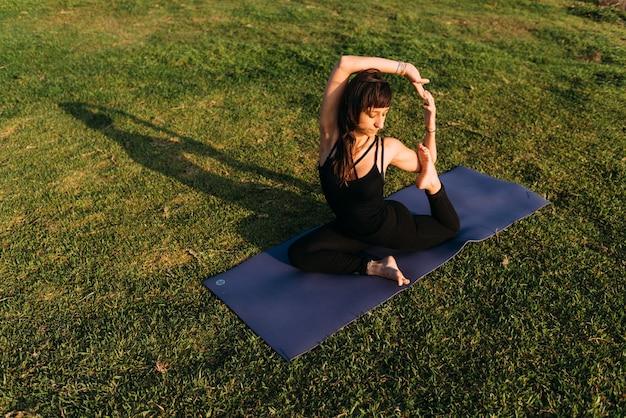 Uma mulher que forma uma figura de ioga sentada em sua esteira na grama fora de sua casa. copie o espaço