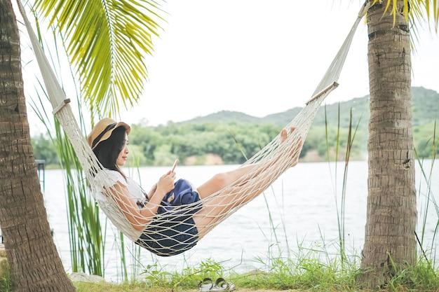 Uma mulher que joga o telefone celular na rede sob a árvore de coco durante o feriado.