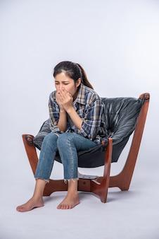 Uma mulher que se sente desconfortável e se senta em uma cadeira
