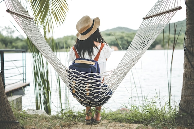 Uma mulher que senta-se na rede sob a árvore de coco durante o feriado.