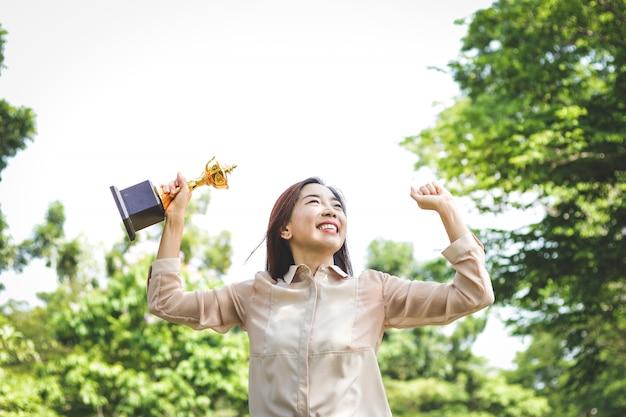 Uma mulher que trabalha em um escritório, segurando um troféu levante as duas mãos, feliz