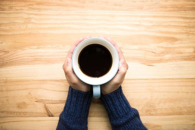 Uma mulher que veste uma camisa azul que guarda uma xícara de café azul com suas mãos.