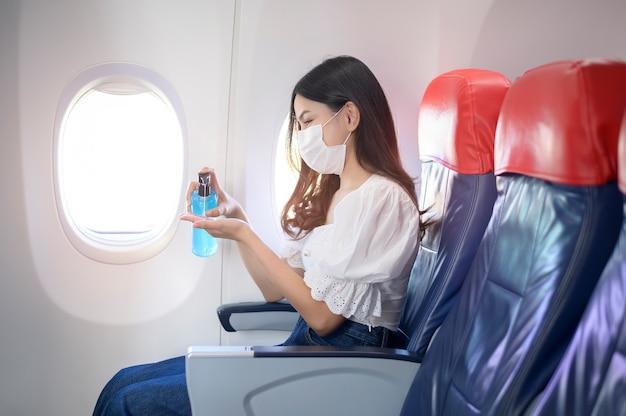 Uma mulher que viaja usando máscara protetora está lavando as mãos com álcool gel a bordo