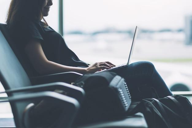Uma mulher que viaja usando um laptop enquanto está sentada no aeroporto