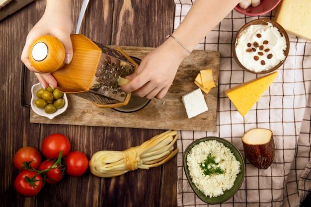Uma mulher ralar queijo em uma placa de madeira com azeitonas em conserva tomates frescos e vários tipos de queijo na vista superior de madeira