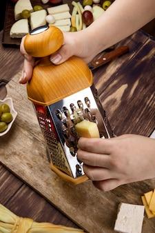 Uma mulher ralar queijo em uma placa de madeira com azeitonas em conserva vista lateral