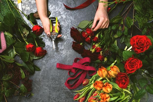 Uma mulher recolhe um buquê de flores da primavera em uma mesa de pedra. florista no local de trabalho