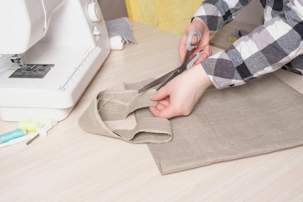 Uma mulher recorta os detalhes de uma bolsa ecológica, uma compradora de linho natural com as próprias mãos, uma máquina de costura e materiais para costurar na mesa