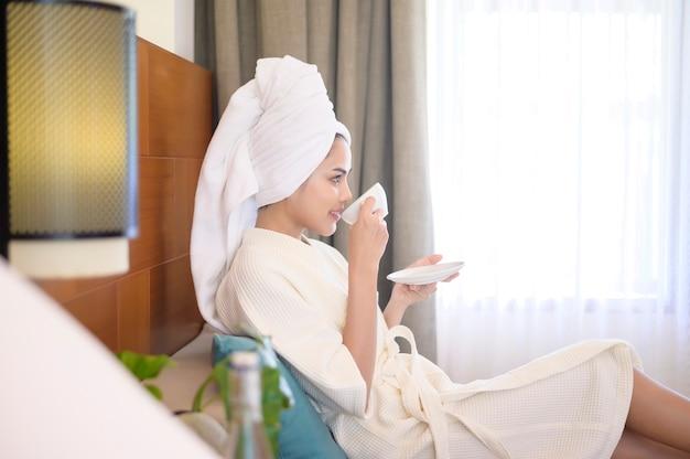 Uma mulher relaxada vestindo um roupão de banho branco e uma toalha tomando um café pela manhã