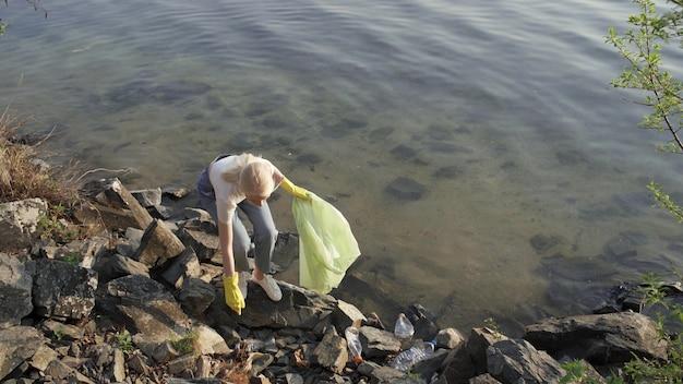 Uma mulher remove o lixo entre as pedras perto do lago. a mulher pega o lixo espalhado e coloca em um saco de lixo. limpando o meio ambiente. 4k uhd