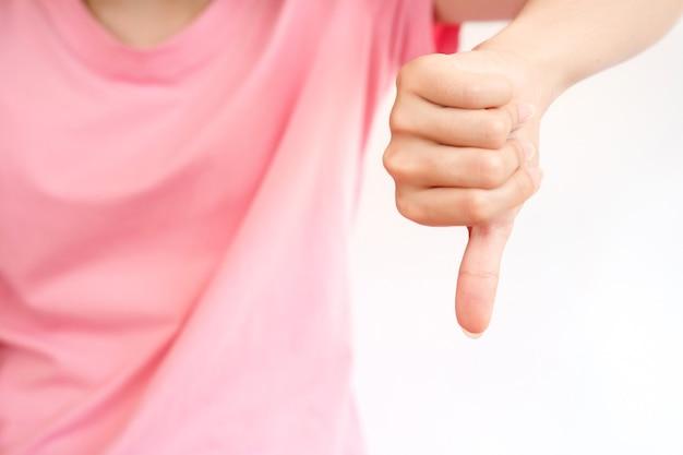 Uma mulher se expressa em linguagem de sinais com os polegares para baixo. a mídia mostrou que o que foi encontrado era ruim.