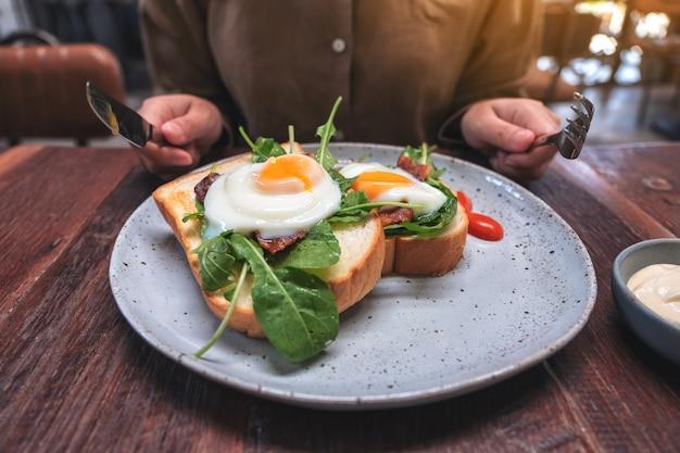 Uma mulher se preparando para comer um sanduíche de café da manhã com ovos, bacon e creme de leite por faca e garfo em um prato na mesa de madeira