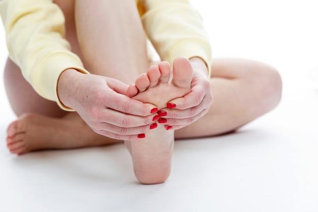 Uma mulher se senta no chão e segura o pé com as mãos. autoajuda para contração muscular. fundo branco. espaço para texto.