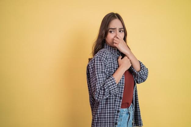 Uma mulher se sente desconfortável porque sente o cheiro ruim cobrindo o nariz com a mão enquanto est ... Foto Premium