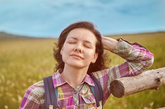 Uma mulher se virou para o sol com os olhos fechados.