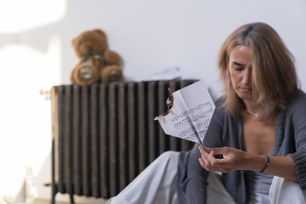 Uma mulher segura nas mãos um avião aceso, feito de uma folha de papel com notas musicais