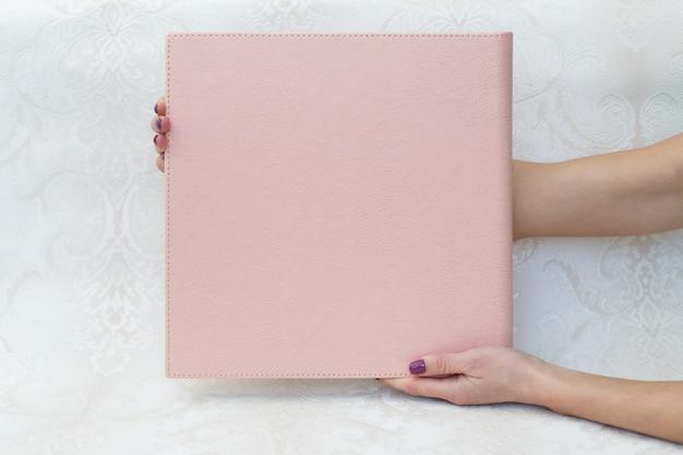 Uma mulher segura um álbum de fotos da família. a pessoa olha para o livro de fotos. amostra de álbum de fotos rosa. álbum de fotos de casamento com capa de couro.
