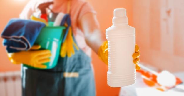 Uma mulher segura um balde de produtos de limpeza em casa, segurando uma garrafa branca vazia