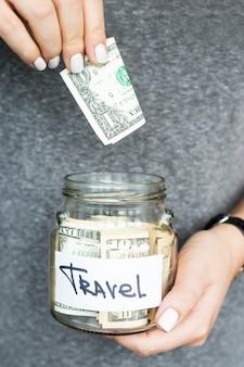 Uma mulher segura um cofrinho com dólares para viajar e coloca mais dinheiro. acumulação do conceito de finanças