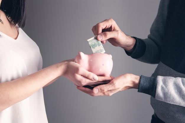Uma mulher segura um cofrinho e um homem coloca dinheiro. acumulação de conceito de fundos em cinza