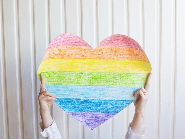Uma mulher segura um coração de arco-íris na parede branca símbolo da comunidade lgbt