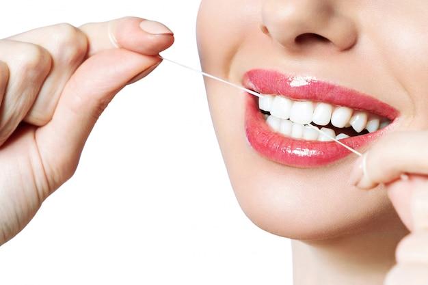 Uma mulher segura um fio dental