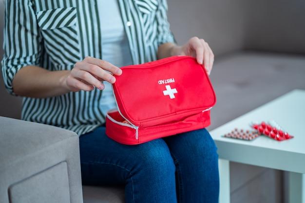 Uma mulher segura um kit de primeiros socorros com remédio em casa