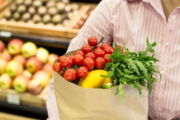 Uma mulher segura um saco de papel com legumes e frutas em suas mãos.