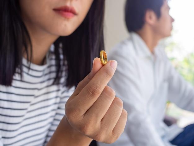 Uma mulher segura uma aliança e pensa muito depois de discutir com o marido.