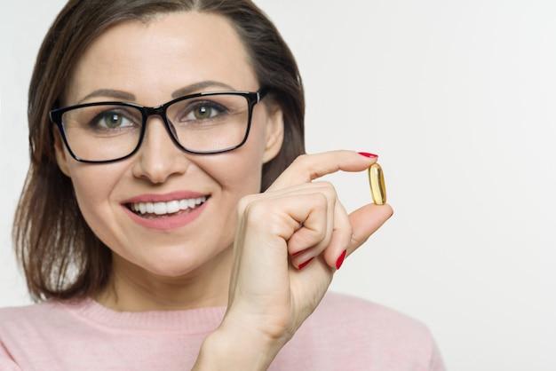 Uma mulher segura uma cápsula com vitamina e, óleo de peixe.