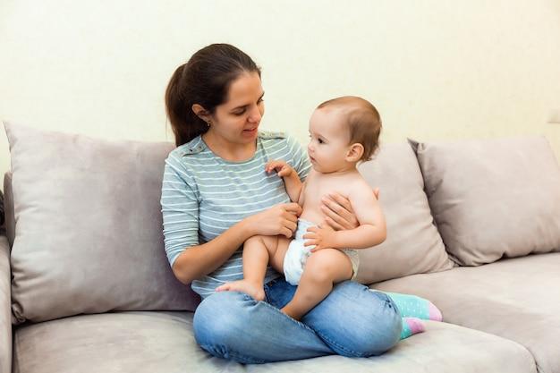 Uma mulher segura uma criança nos braços e lê um livro para ela. mãe e filho no sofá.