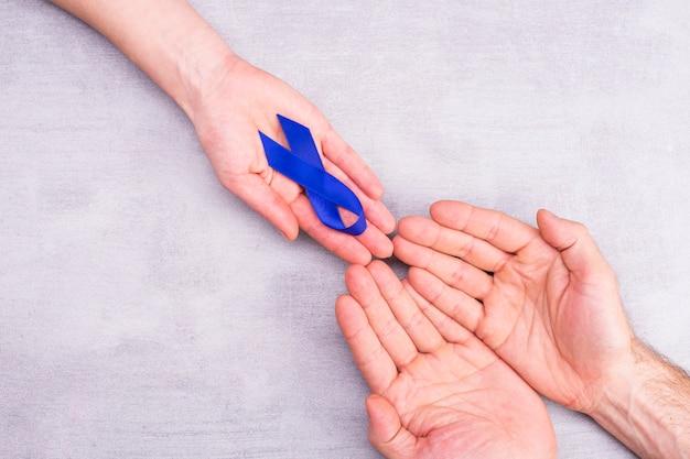 Uma mulher segura uma fita azul de conscientização