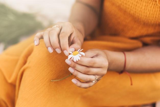 Uma mulher segura uma flor de margarida nas mãos e arranca as pétalas.